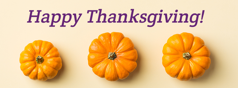 Three pumpkins on a table with text, HAPPY THANKSGIVING!