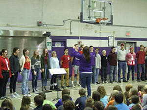 Wide view of Show Cats performing for students with a conductor