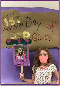 Female student wearing a mask holding a sign with Mrs. Wandless's photo on it in front of a 1st day of school poster