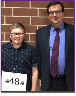Adult standing with a spelling bee contestant
