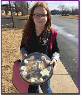 Student holding a large cookie with the Pi math symbol on it