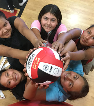 Female students hold up a volleyball in a gym