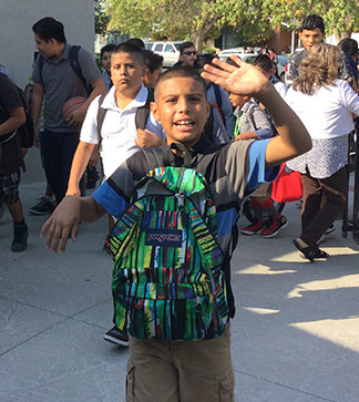 Waving student poses outside