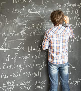 Student writes equations on a blackboard
