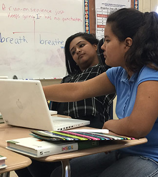 Two female students use laptops in class