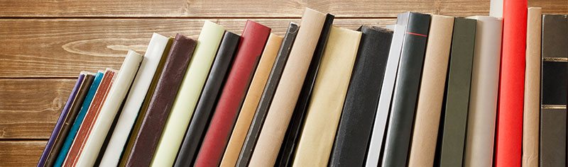 Books leaning against each other in front of a wood background