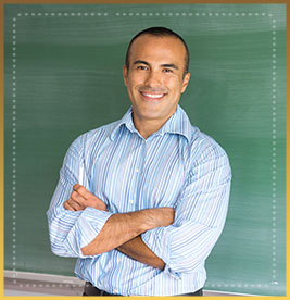 Teacher stands in front of chalkboard with arms crossed