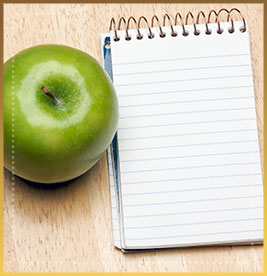 Notebook and apple on wood background