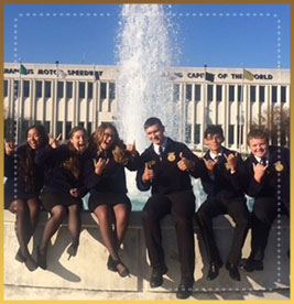Students pose in front of a fountain