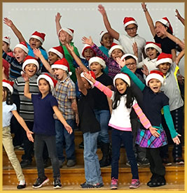 Students wearing santa claus hats dance together