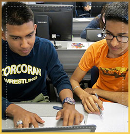 Two students look at computer