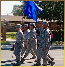 ROTC students marching outside with blue flag