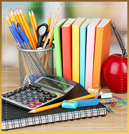 Notebooks, pens, pencils, a calculator, an apple, paperclips and erasers on a wood table