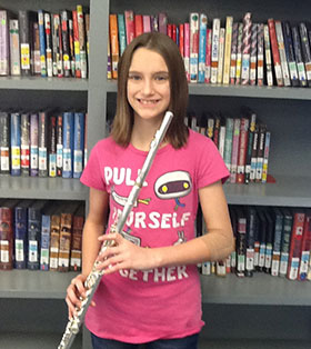 Female student holds a wind instrument