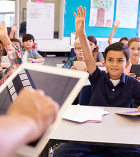 Students raise their hands in class