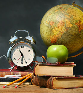 An apple, clock, globe, books, pencils, and glasses sit on a wood surface
