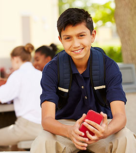 Smiling male student wearing a backpack poses outside