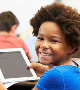 Smiling student uses a tablet in class