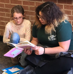 student and adult reading together