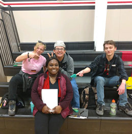 Four students sitting on the gym bleachers