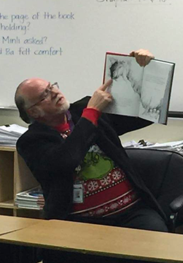 Male teacher showing class a book from his desk