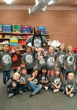 Kindergarten and 1st grade students showing off new shirts