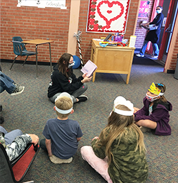 Teacher reading to students in the classroom on the floor