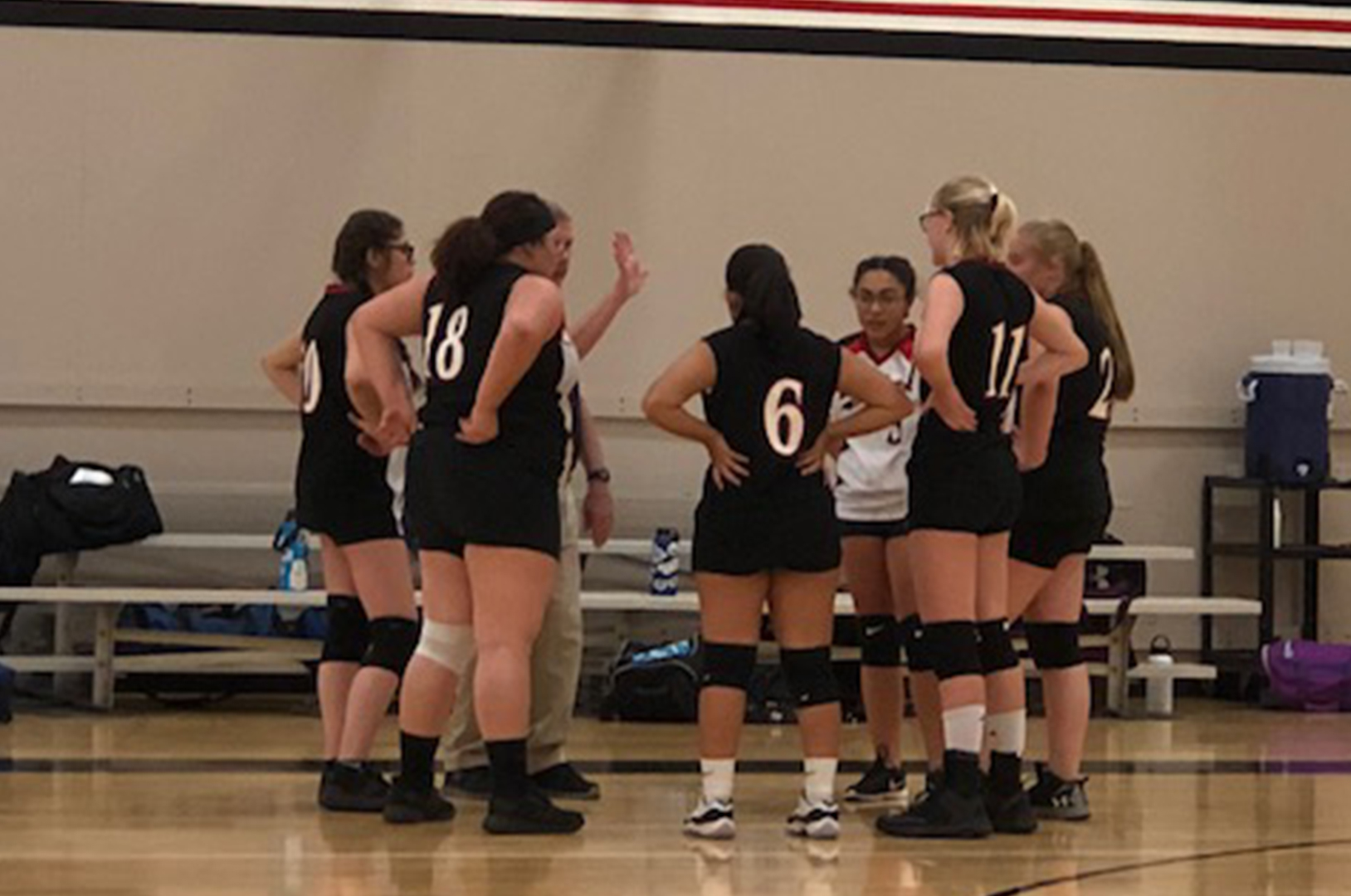 Girls volleyball team in a huddle during a game
