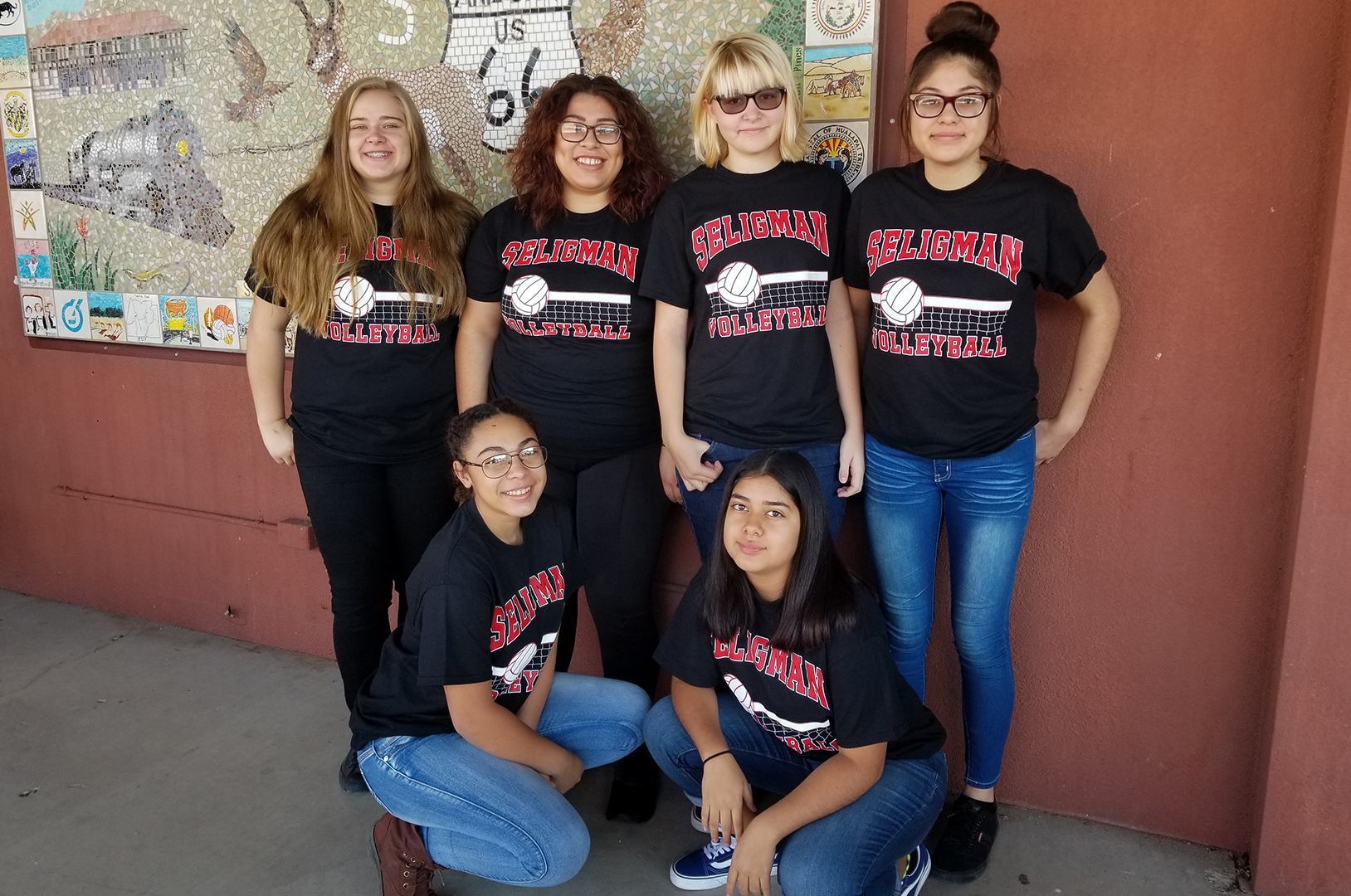 Group of six happy members of the girls volleyball team wearing their SELIGMAN t-shirts