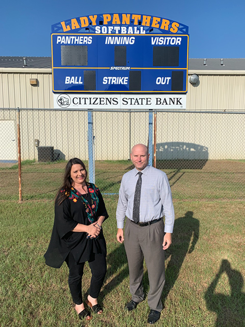 Amy Smith and Superintendent Russell Holden standing in front of new scoreboard