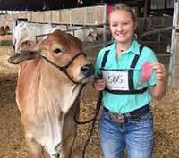 Kailey Bean poses with a cow and her award