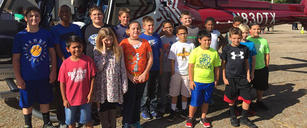 Oakwood Elementary students in front of a helicopter