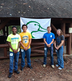 Four students pose together with a banner of a duck hanging behind them