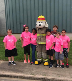Firefighter dog mascot standing with students