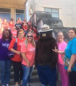 Smokey the Bear standing with a few teachers