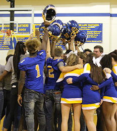 Football players and cheerleaders hold up football helmets while cheering