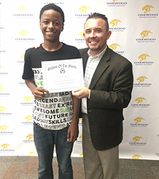 Male student poses with a teacher as he holds his award
