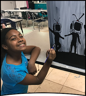 Student paints on a canvas
