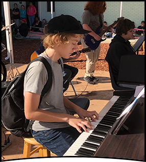 Student plays piano outside