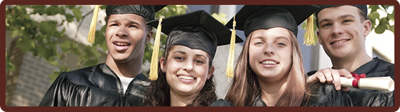 Four graduates pose together wearing graduation attire and holding a diploma