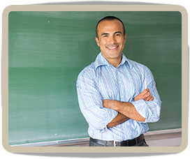 Teacher poses in front of a blackboard
