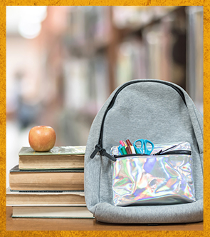 Backpack, books, an apple on a table in a library