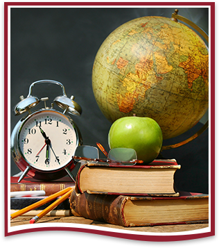 Apple stacked on top of books with a clock, glasses and a globe next to it