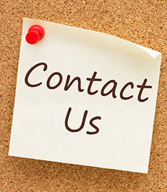 Contact Us written on a piece of paper attached to a cork board with a pushpin