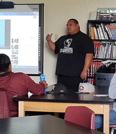 Staff member talking to students and using a projector