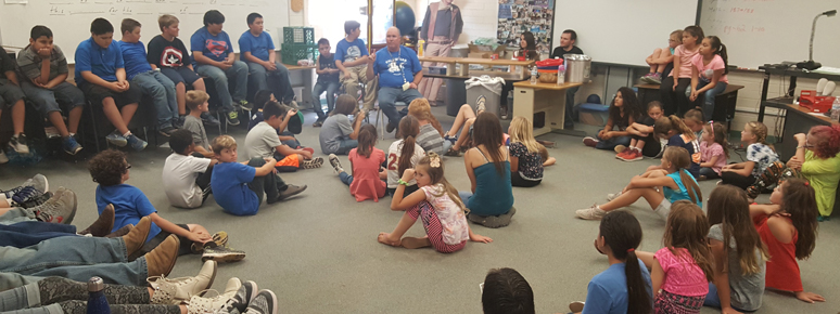 Students gathered in a circle listening to a teacher