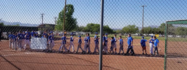 Baseball team giving high fives to opposing team