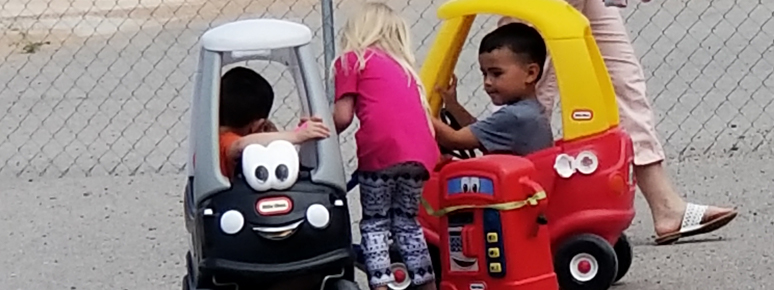 Preschool children playing with cars on the playground