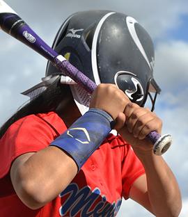 Baseball player holds a baseball bat on a field