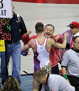 Wrestling coach and wrestler hug each other
